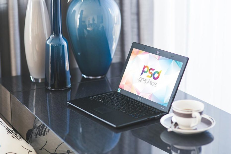 A black laptop on table Mockup with a cup of tea