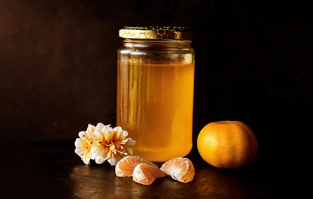 Honey jar with orange and flowers