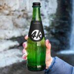 Free Glass Bottle in Hand Mockup